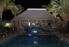 Swimming pool with waterfall at night