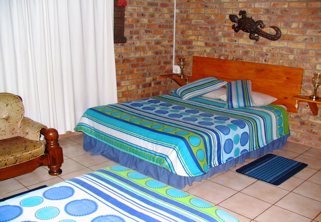 Queen size bed in Chalet One with single bed visible in foreground